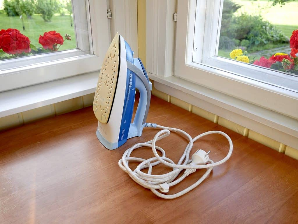 A steam iron on the floor with tangled cords