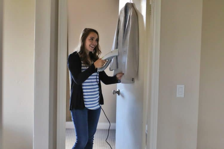 A woman steam cleans a suit jacket with a smile on her face