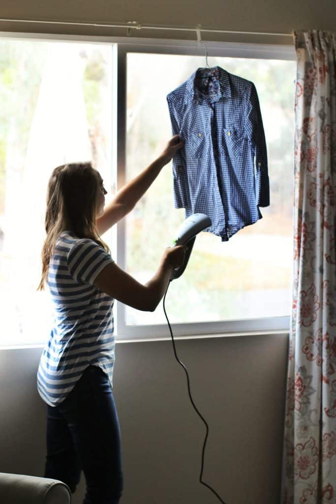 A woman uses a handheld steamer to steam a shirt hanging in the window
