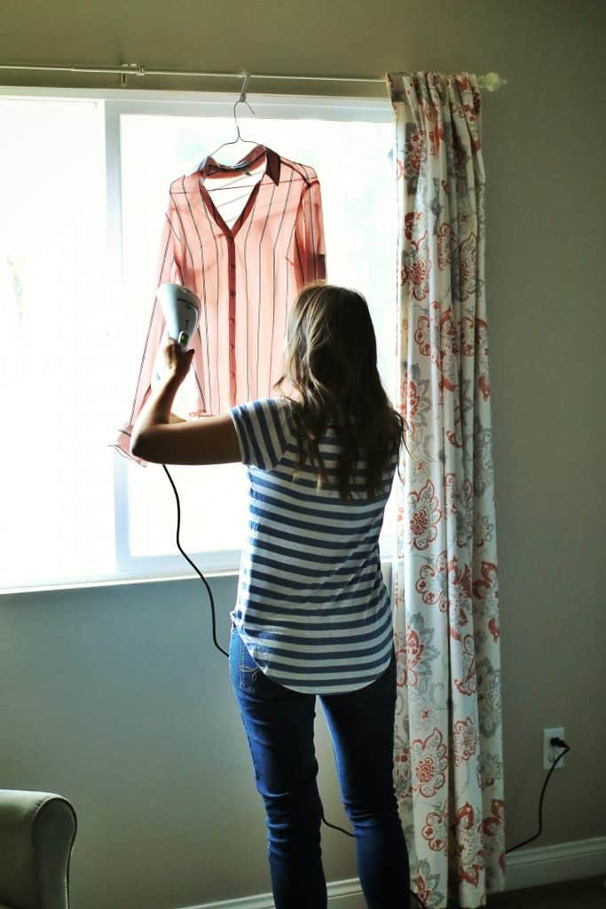 A woman uses a portable steamer on a pink shirt